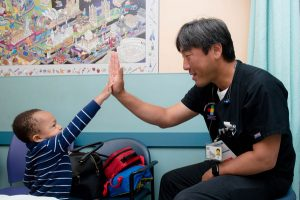 dr. peng gives a child a high-five