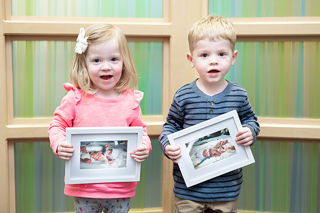 two children holding photos of themselves when they were in the NICU