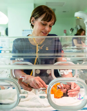 nicu nurse tending to newborn