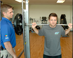 sports physical therapist working with patient on weights