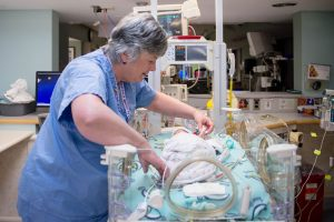 nurse caring for baby in nicu