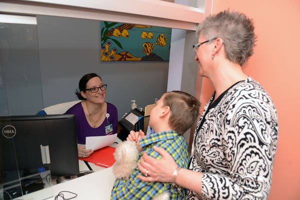 Receptionist greeting parent and child