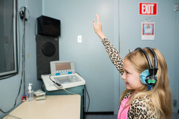 patient raising hand during hearing test