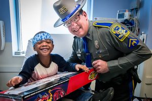 state trooper giving toy to patient