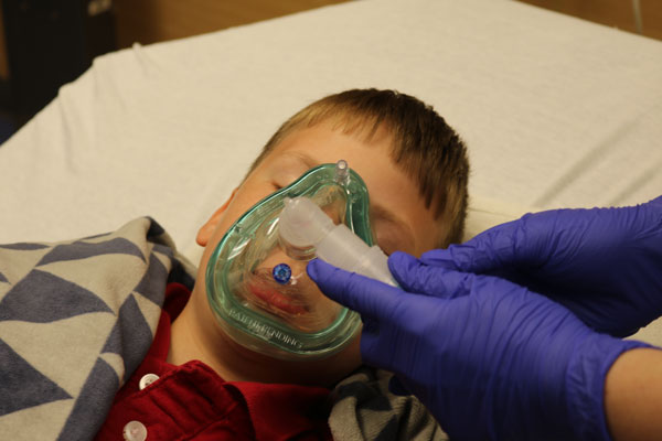 nurse applying sedation mask