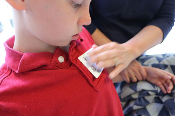 boy putting visitor sticker on shirt