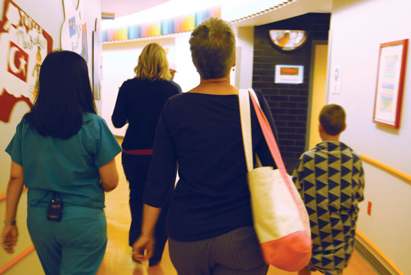 child and parent walking hallway to sedation