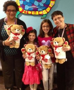 Gabriella and sister Francesca deliver teddy bears to Dr. Heller, Cardiologist and Patricia McIntosh of Child Life