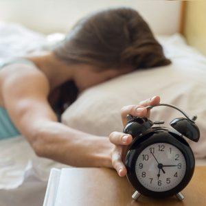 teen hitting snooze button