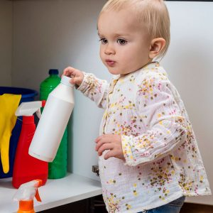 child reaching for cleaner in cabinet