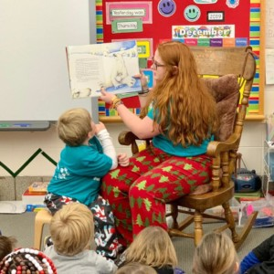children wearing pjs and listening to a book