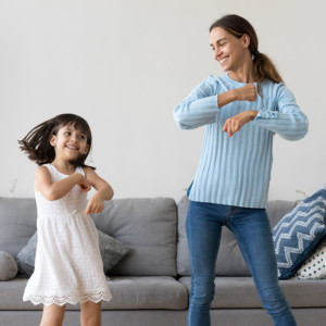 Mom and daughter dancing in front of a grey couch in their living room.