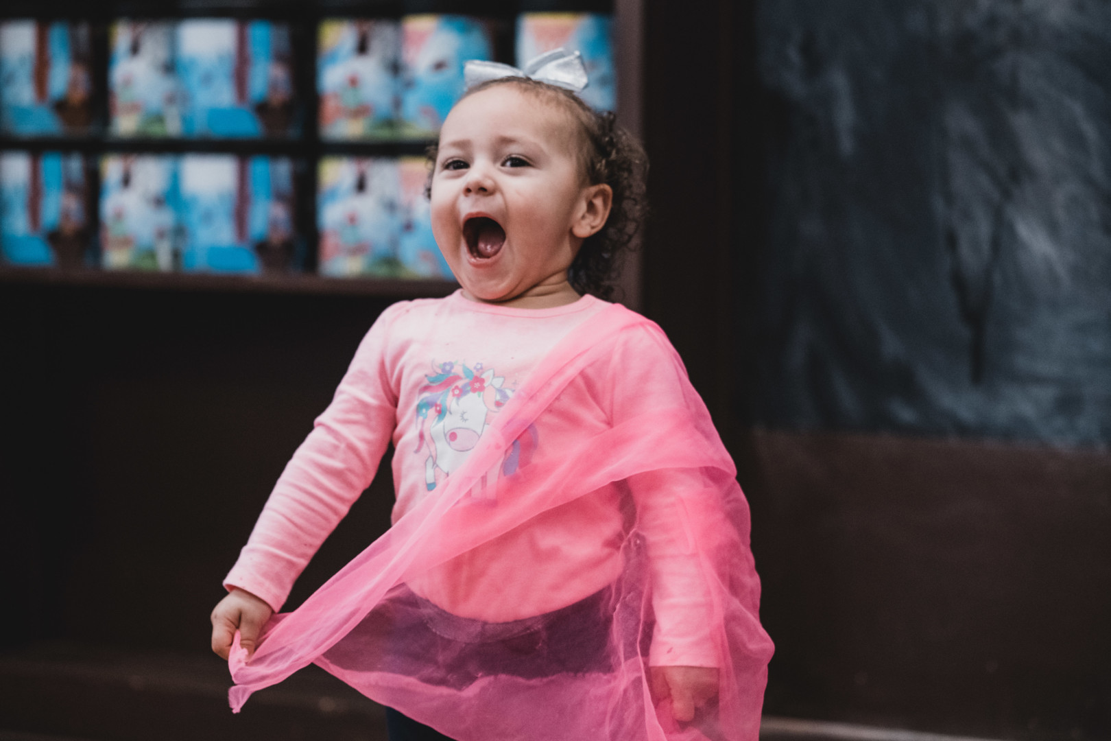 Child participating in Zumbini class plays with scarf