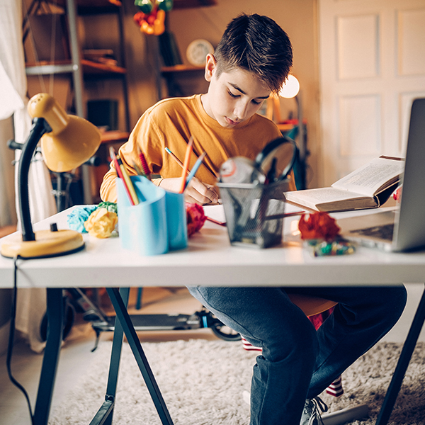 Young boy completed school work at desk at home