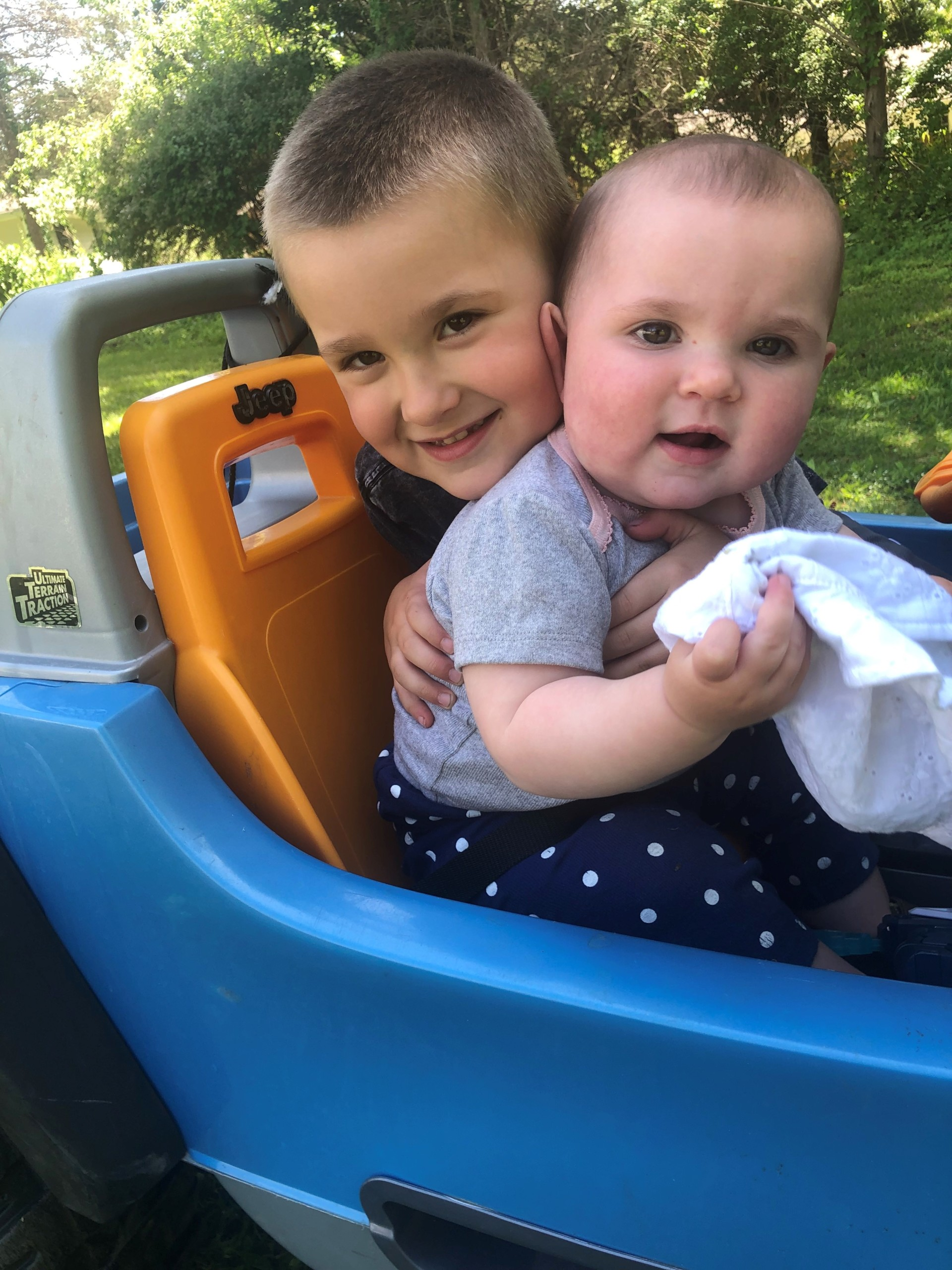 Esmae and Oliver, two patients in ENT, ride in a toy car.