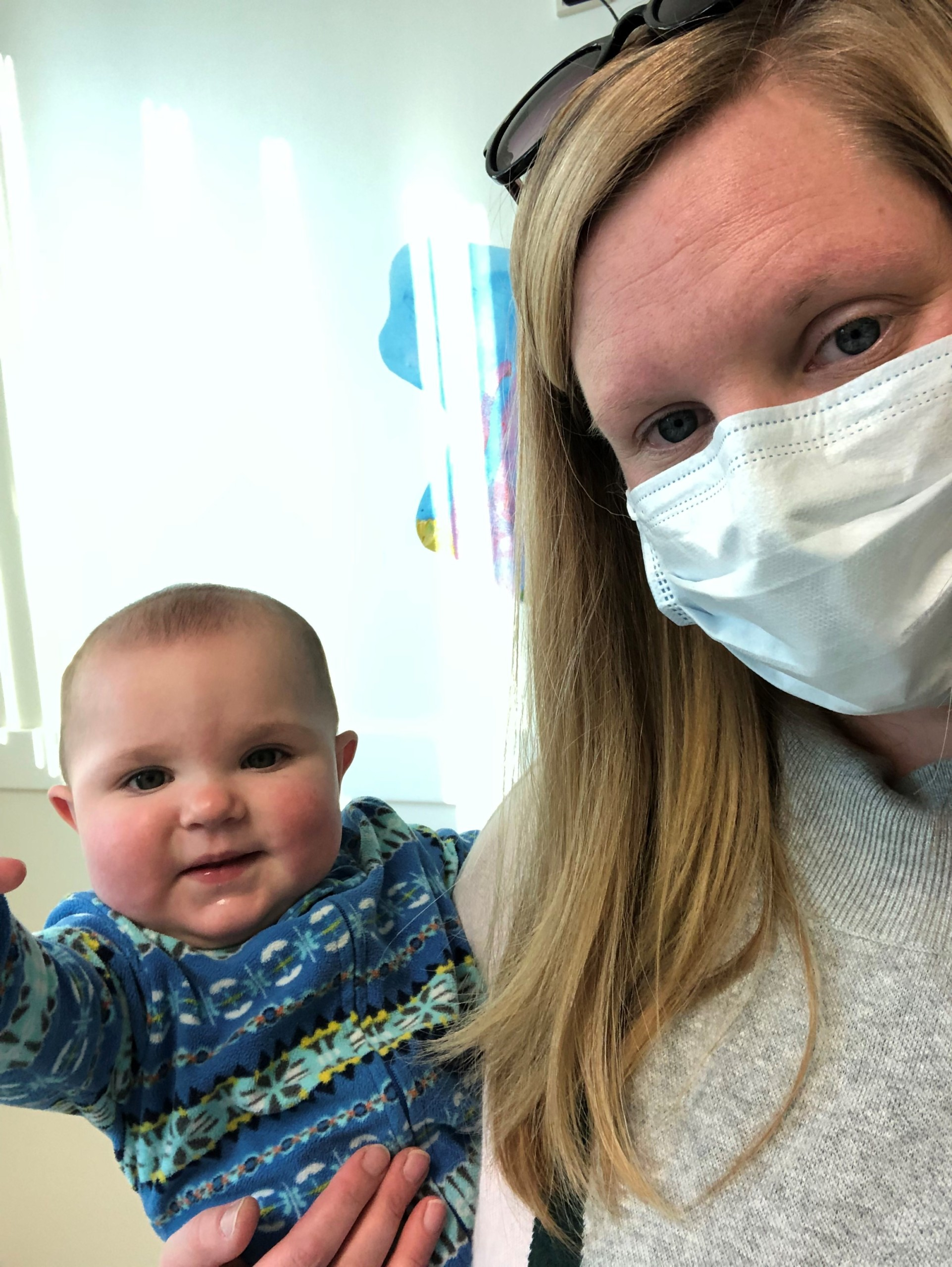 Esmae waits for her ear tube surgery with her mom.