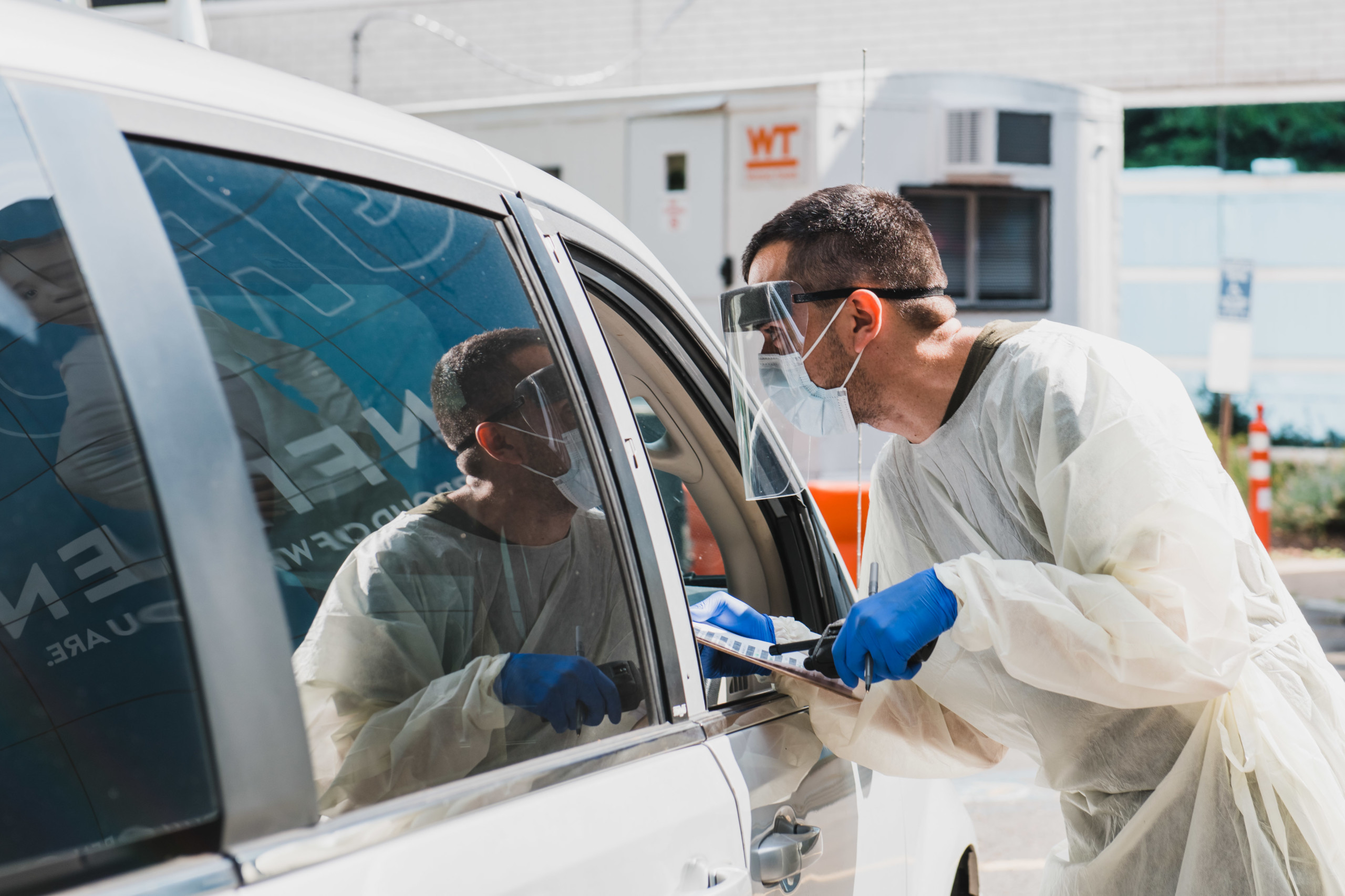 Team member in full PPE hands paperwork to family during drive-through COVID-19 testing