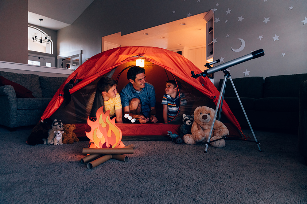 Dad and sons set up tent in living room