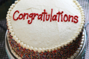 Cake with vanilla frosting. Congratulations piped on it. Multi-colored sprinkles all around