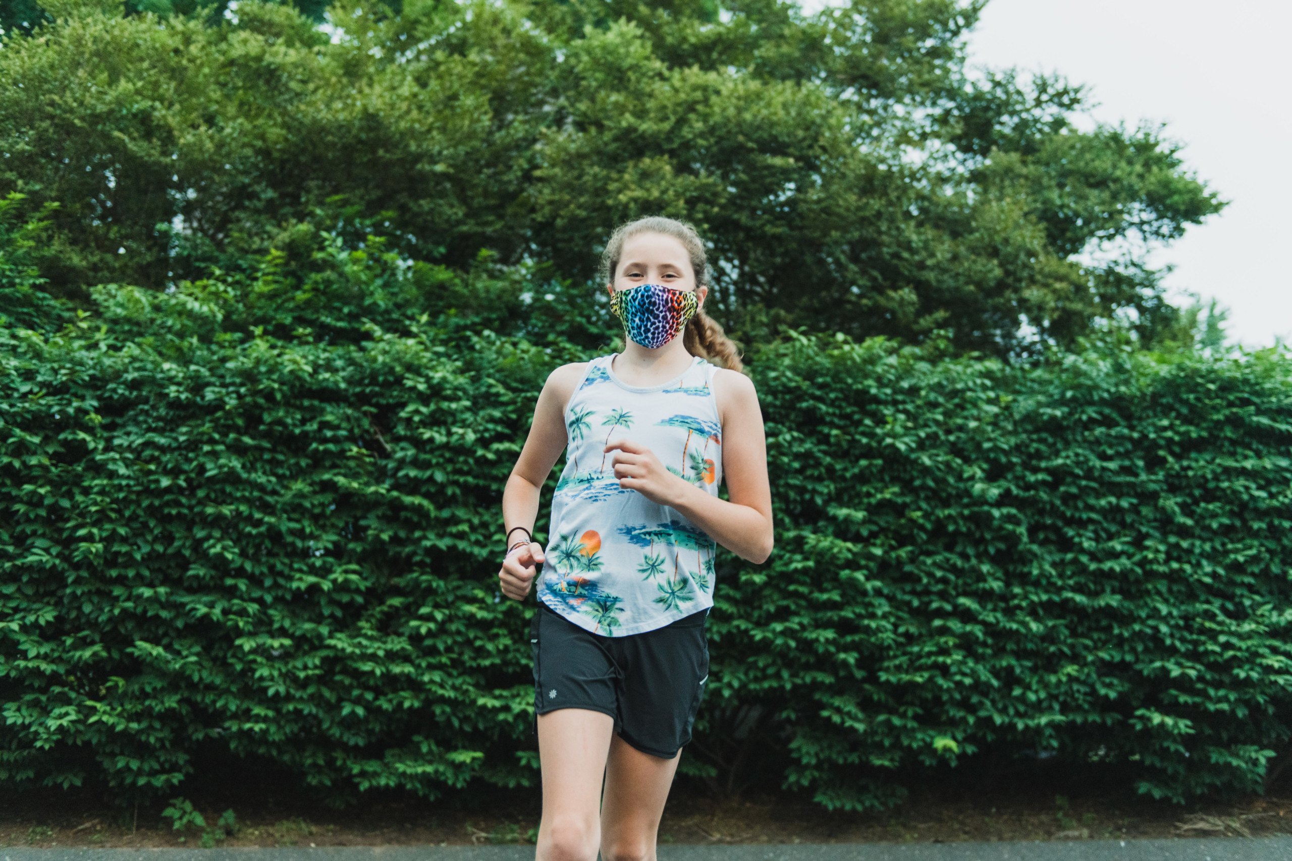 Teen wearing face mask while running.