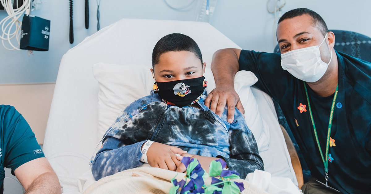 Patient and father wear masks in a hospital room