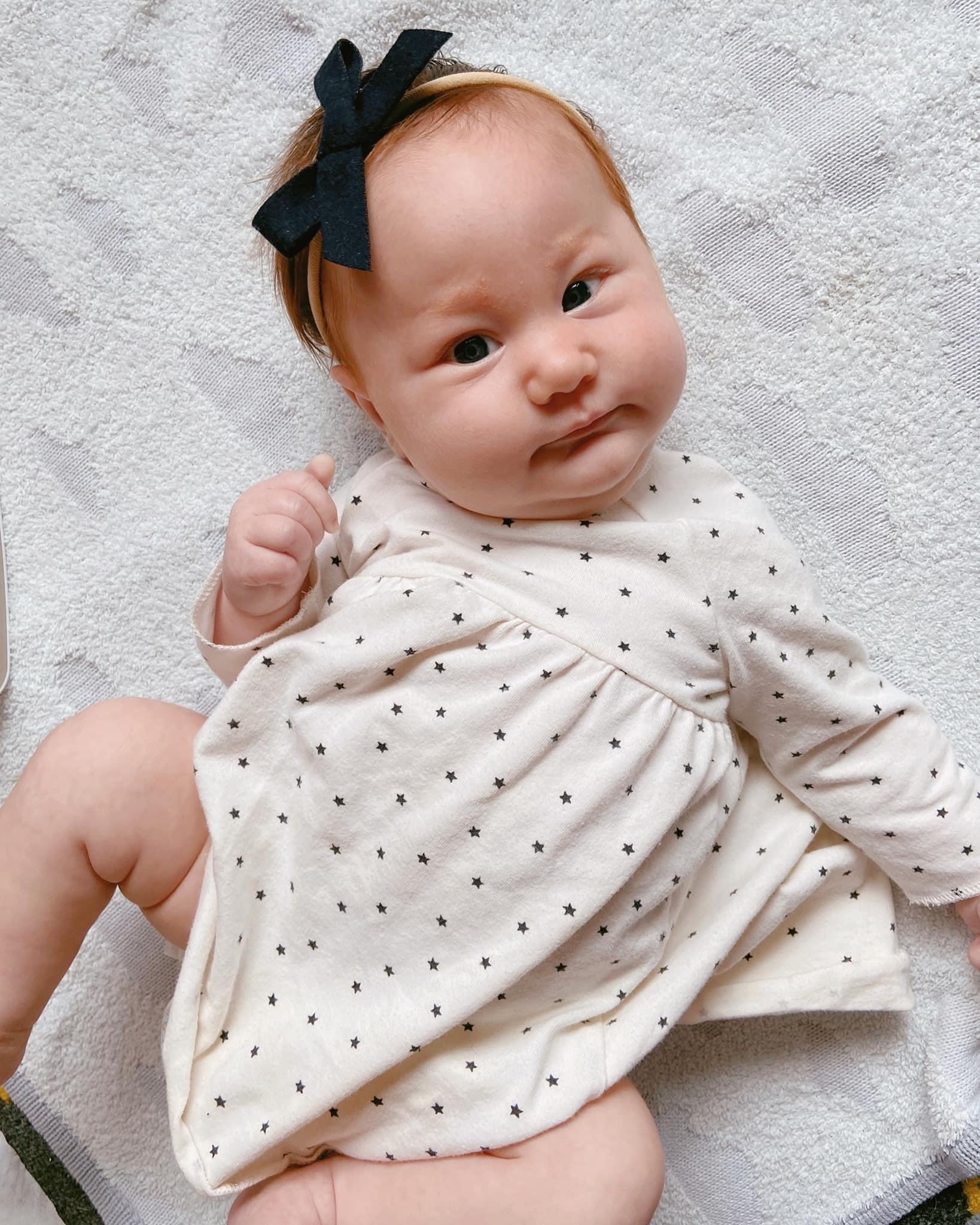 Newborn patient Emilia wearing a polka dot onesie