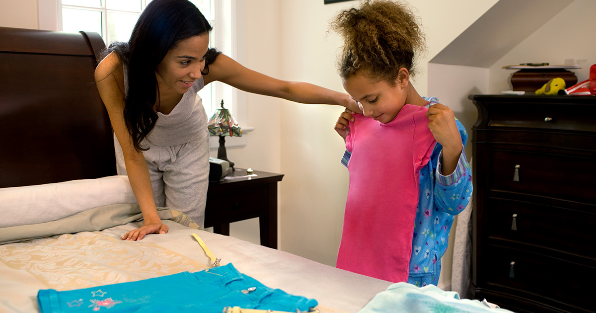 Mom helps daughter select outfit the night before school