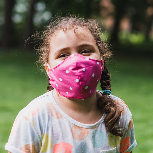 School-age girl wears purple mask outside.