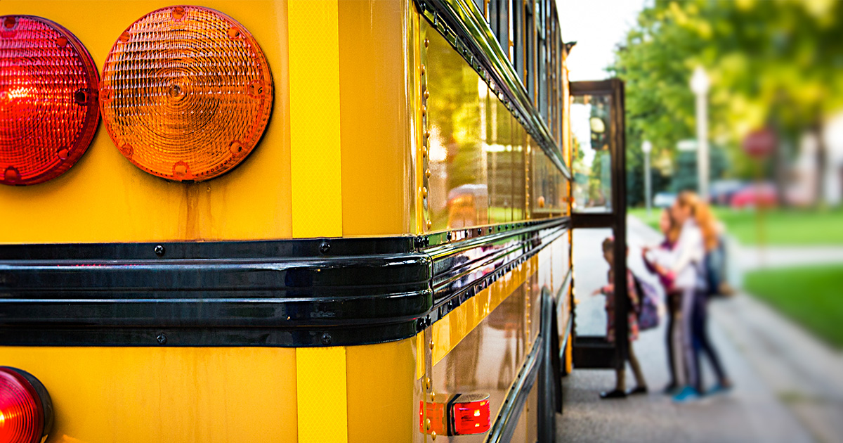 Yellow school bus in foreground, while school-age children board the bus out of focus in the background
