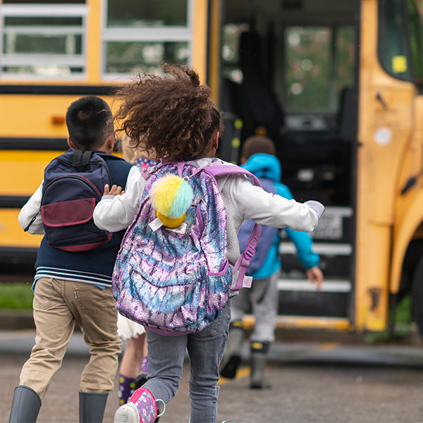 Group of school-age children board the bus