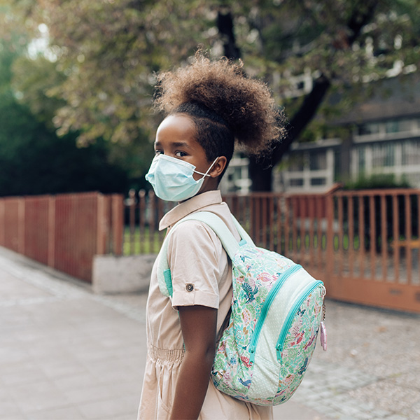 Pre-teen girl walking to school with a backpack and face mask