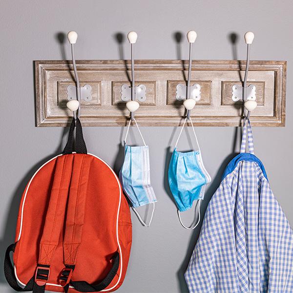 Backpack, bag, and face masks hung on coat hooks