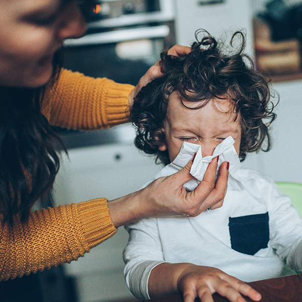 Mom holds tissue as boy blows his nose