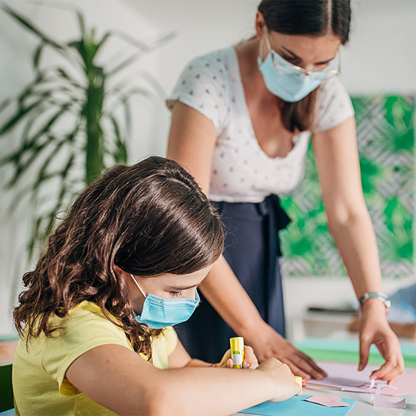 Teacher provides help to young student. Both teacher and student are wearing face masks