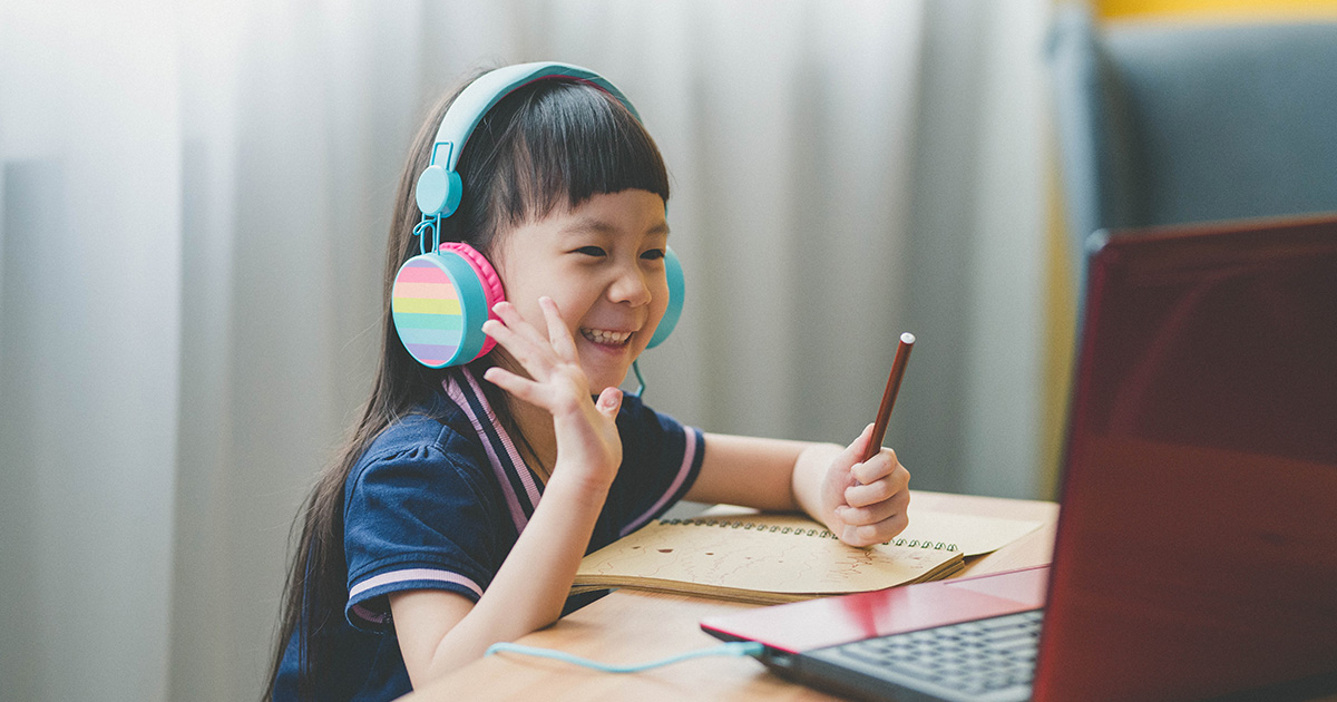 Girl waves at laptop screen during distance learning