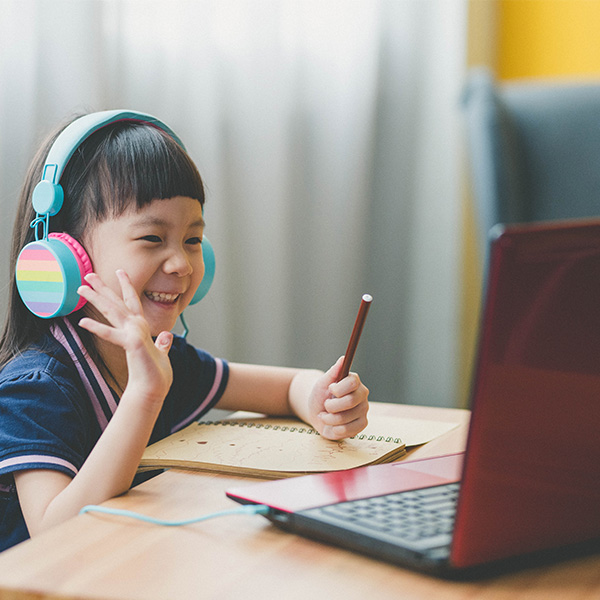 Girl waves at computer screen while completing distance learning