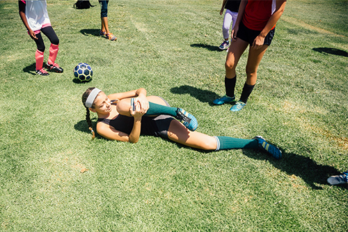teenage soccer player laying in the field holding an injured knee