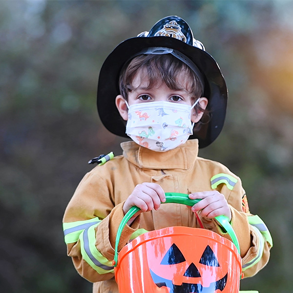 Young boy wears firefighter costume and face mask while trick-or-treating