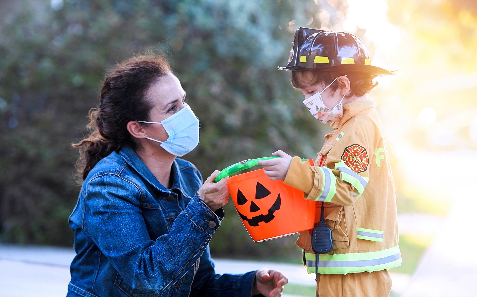 Woman and child wearing face masks; child is wearing a firefighter costume and holding a plastic bucket while preparing to go trick-or-treating