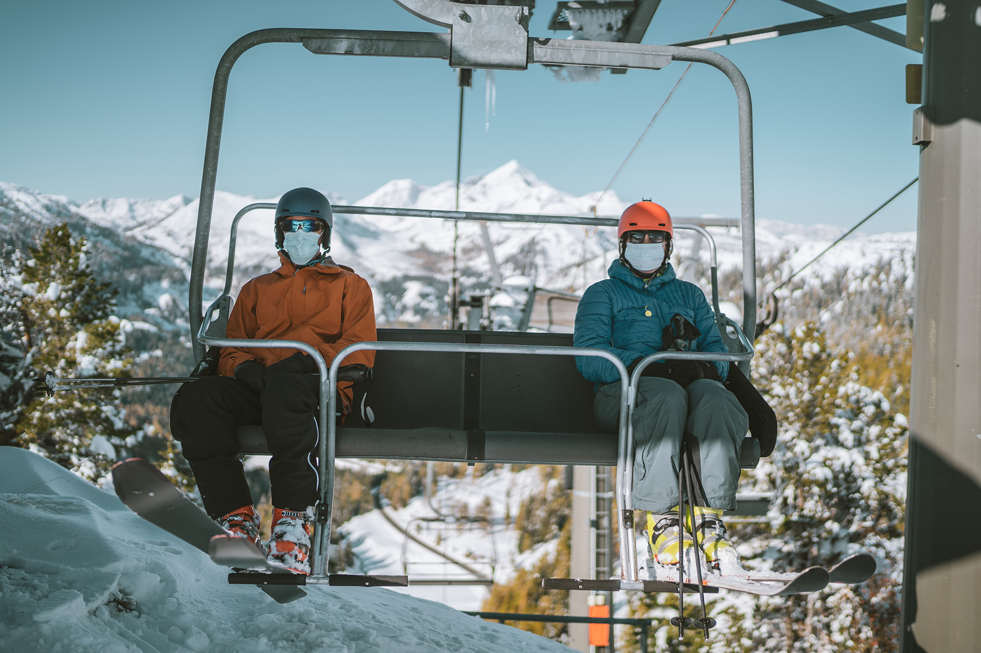 Two skiers ride a chairlift while wearing snow gear and masks
