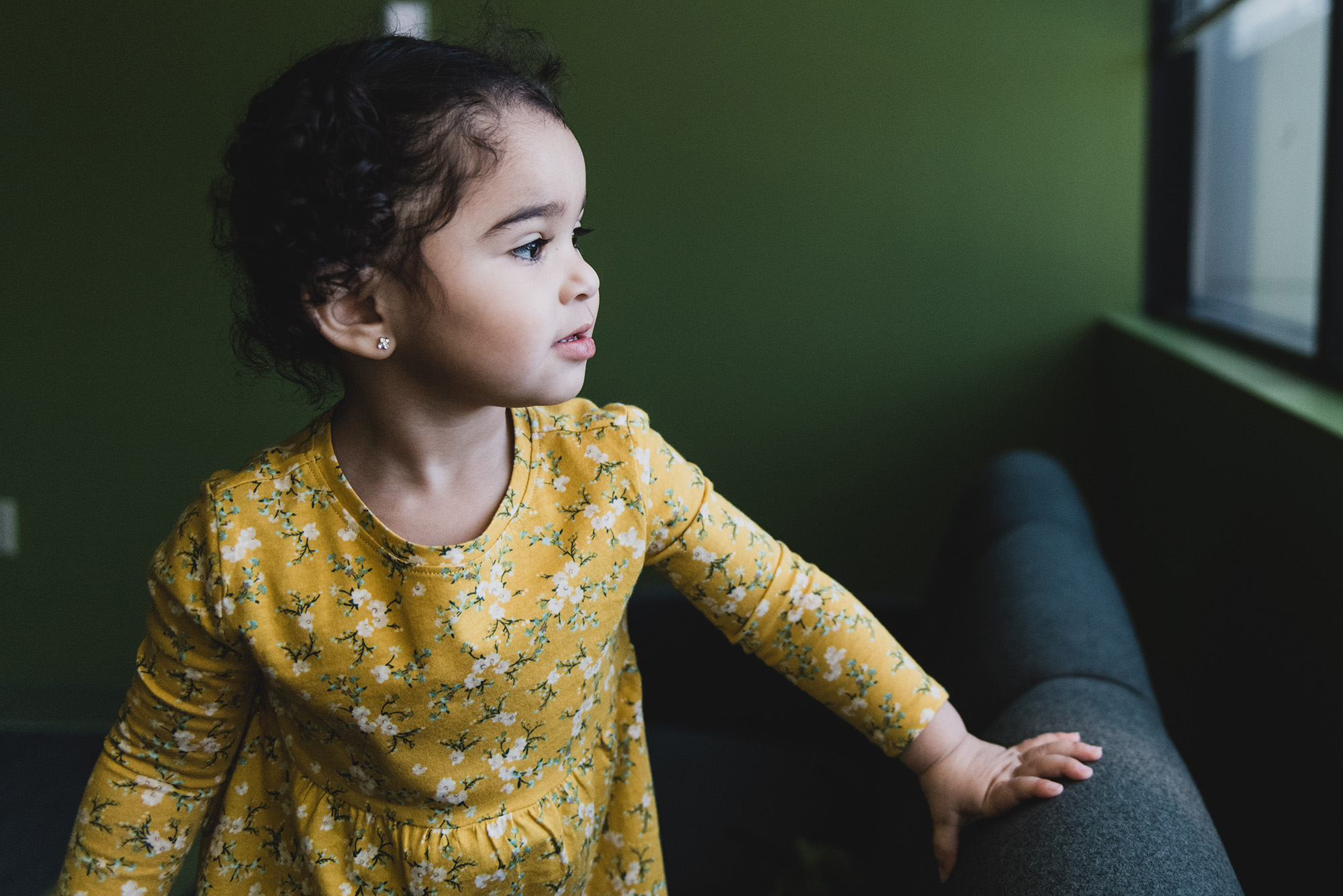 Urology patient Natalia looks out the window while wearing a yellow dress
