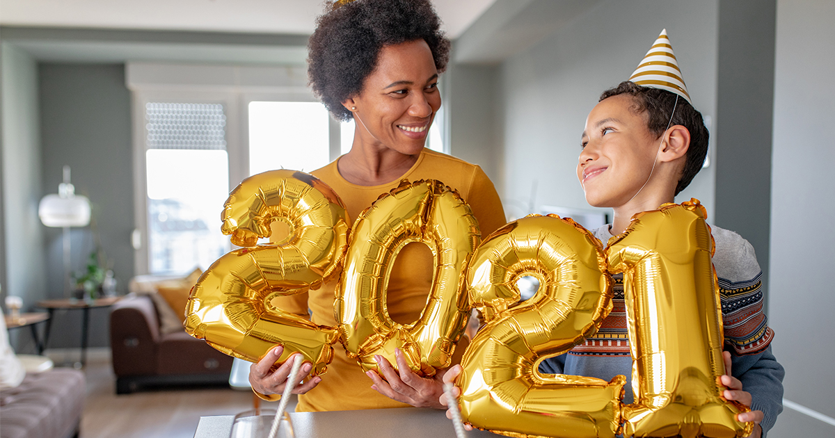 Mother and son hold up 2021 balloons