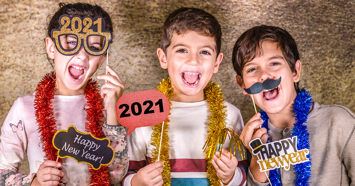 Two boys and a girl pose in a photobooth with New Years Eve props for 2021