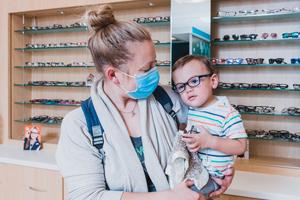 parent holding child inside optical shop