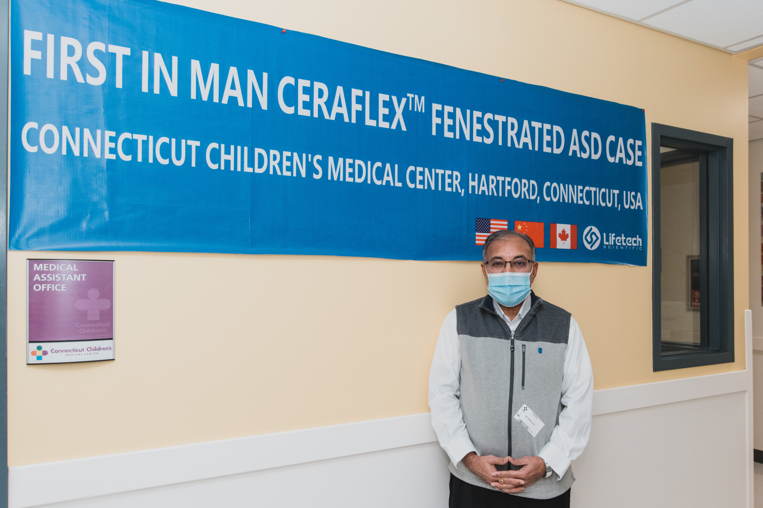 "Patient Haresh Surti stands in front of a banner that says ""First in man Ceraflex Fenestrated ASD Case"""