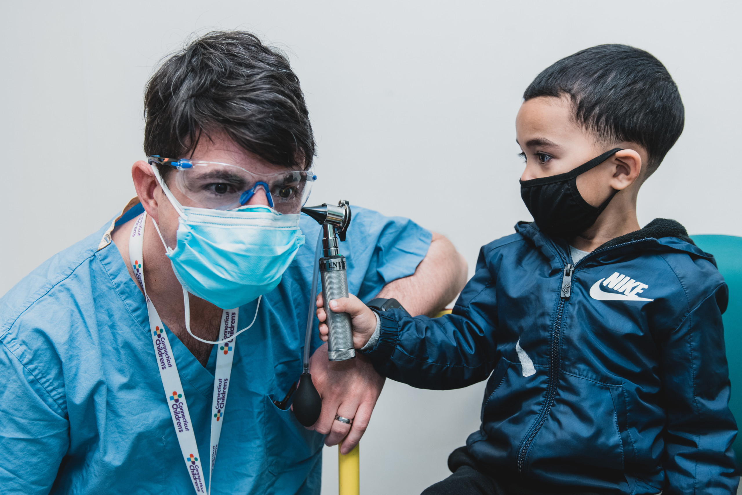 ENT specialist Christopher Grindle, MD, lets patient Cameron Soto look inside his ears