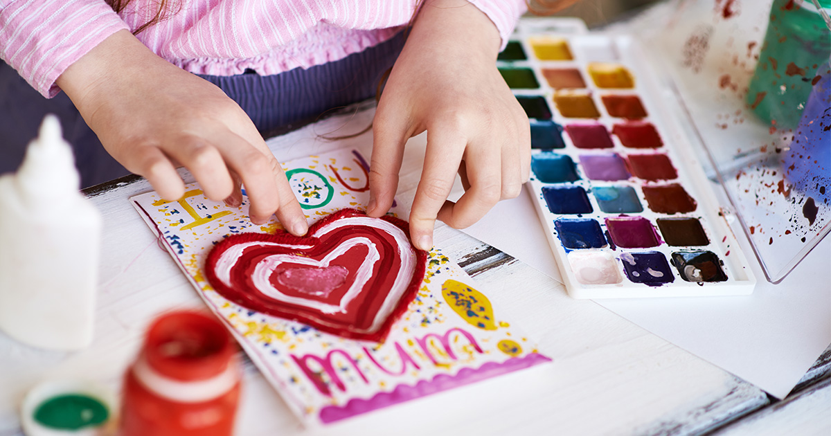 """Young girl assembles handmade Valentine's Day card that reads """"I Love You Mum"""""""