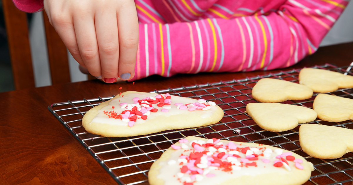 Young girl adds sprinkles to heart-shaped sugar cookies