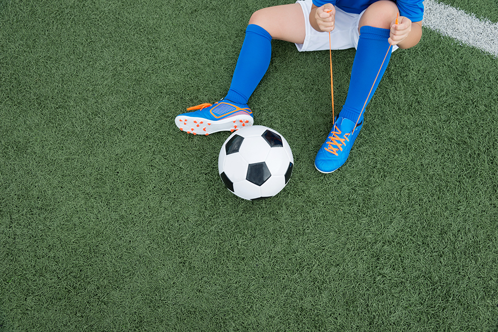 Teen athlete tying soccer cleats