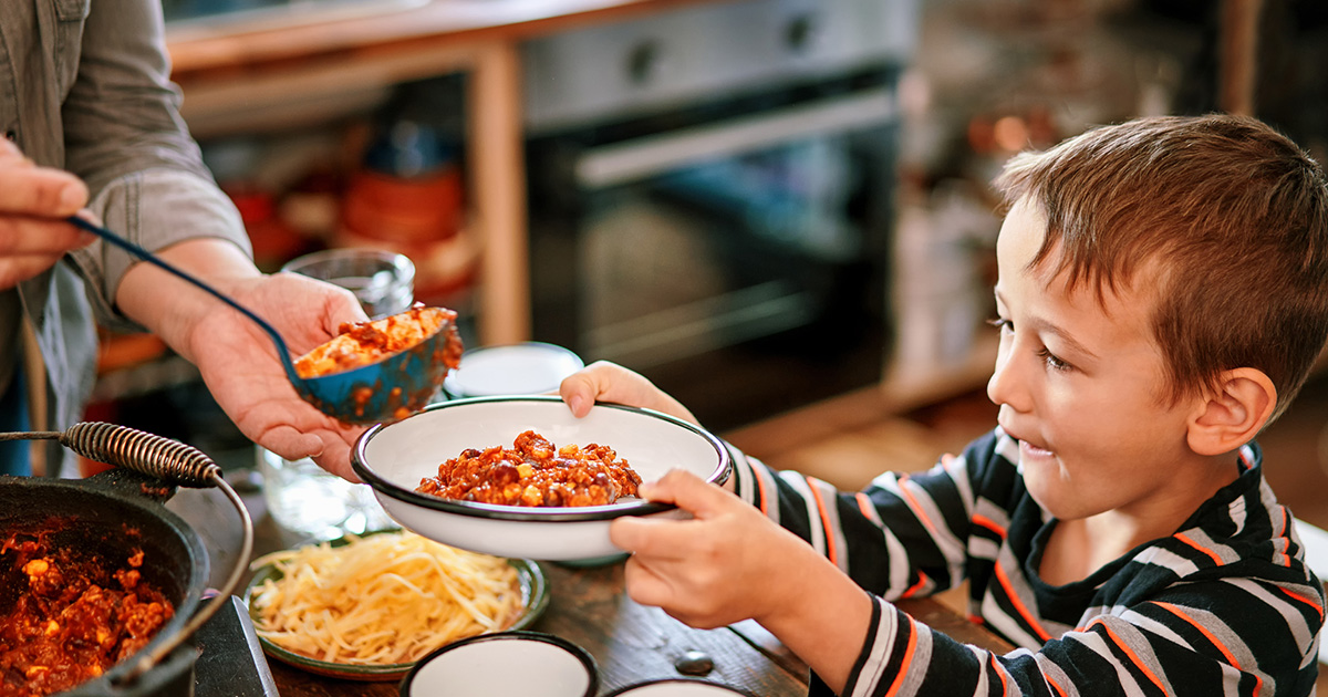 Parent uses a ladle to serve chili to son who is holding a bowl